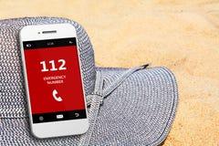 Teléfono móvil con la emergencia número 112 en la playa Fotografía de archivo