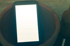 Teléfono móvil con la pantalla blanca en la cocina Fotografía de archivo libre de regalías
