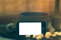 Teléfono móvil con la pantalla blanca en la tabla con las especias Fotos de archivo libres de regalías