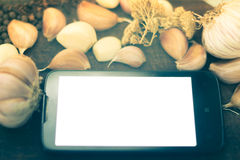 Teléfono móvil con la pantalla blanca en la tabla con las especias Imagen de archivo