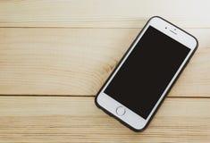 Teléfono móvil con la pantalla en blanco en de madera foto de archivo