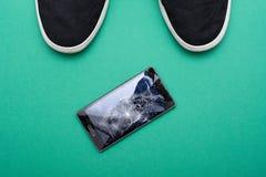 Teléfono móvil con la pantalla quebrada en piso Imagen de archivo