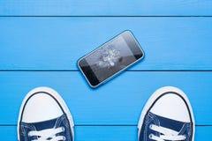 Teléfono móvil con la pantalla quebrada en piso Imagenes de archivo