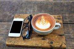 Teléfono móvil con la taza y los vidrios de café del arte del latte Imágenes de archivo libres de regalías