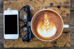 Teléfono móvil con la taza y los vidrios de café del arte del latte Imagenes de archivo