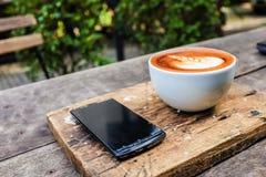 Teléfono móvil con la taza y los vidrios de café del arte del latte Fotografía de archivo libre de regalías