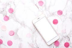 Teléfono móvil con las decoraciones rosadas en un fondo de mármol fotos de archivo