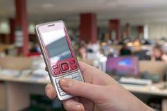 Teléfono móvil contra la perspectiva de la oficina. Foto de archivo