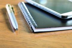 Teléfono móvil, cuaderno y pluma en la madera barnizada Imagenes de archivo