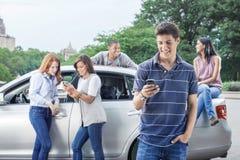 Teléfono móvil de comprobación adolescente con el coche Imágenes de archivo libres de regalías
