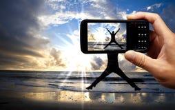 Teléfono móvil de la cámara y hombre de salto feliz