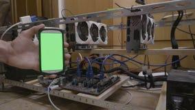 Teléfono móvil de la demostración del ingeniero del programador con la pantalla de visualización verde que conecta con los datos  almacen de metraje de vídeo