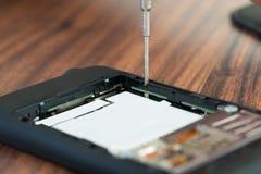Teléfono móvil de la fijación de la mano del técnico foto de archivo