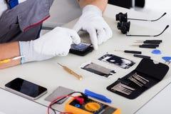 Teléfono móvil de la fijación de la mano del técnico fotografía de archivo libre de regalías