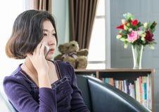 Teléfono móvil de la mujer del uso asiático joven del pelo corto en sala de estar Fotos de archivo