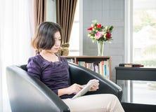 Teléfono móvil de la mujer del uso asiático joven del pelo corto en sala de estar Imagen de archivo libre de regalías