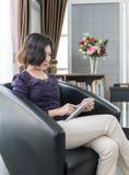 Teléfono móvil de la mujer del uso asiático joven del pelo corto en sala de estar Fotografía de archivo
