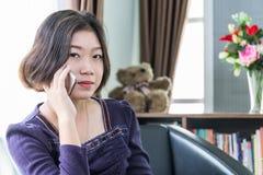 Teléfono móvil de la mujer del uso asiático joven del pelo corto en sala de estar Imagenes de archivo