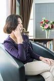 Teléfono móvil de la mujer del uso asiático joven del pelo corto en sala de estar Foto de archivo