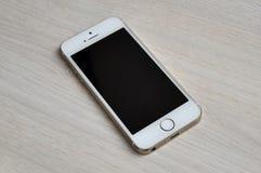 Teléfono móvil de la pantalla en blanco en el fondo de madera Imágenes de archivo libres de regalías