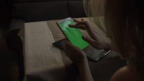 Teléfono móvil de la pantalla verde conmovedora femenina de las manos en el zumo de naranja del fondo almacen de video