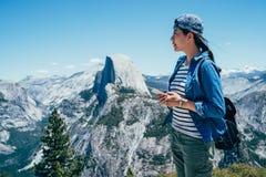 Teléfono móvil de la tenencia del viajero que comprueba la ubicación fotos de archivo