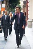 Teléfono móvil de Outside Office On del hombre de negocios Foto de archivo