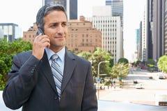 Teléfono móvil de Outside Office On del hombre de negocios Fotos de archivo