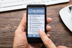Teléfono móvil de Person Hands Filling Checklist On Foto de archivo