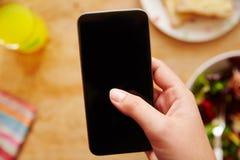Teléfono móvil de Person At Lunch Looking At Imagen de archivo