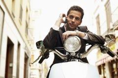 Teléfono móvil de On Scooter Using del hombre de negocios foto de archivo libre de regalías