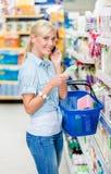 Teléfono móvil del ingenio de la muchacha en la tienda que elige los cosméticos Fotografía de archivo