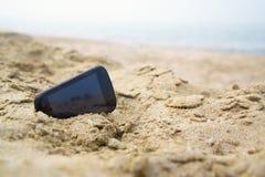 Teléfono móvil del tacto en arena en una playa Fotos de archivo libres de regalías