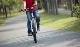Teléfono móvil del uso del ciclista mientras que monta la bici Imagen de archivo libre de regalías