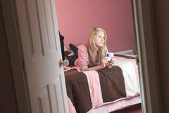 Teléfono móvil del uso del adolescente en su sitio Foto de archivo