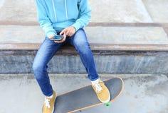 Teléfono móvil del uso del skater en el skatepark Fotos de archivo