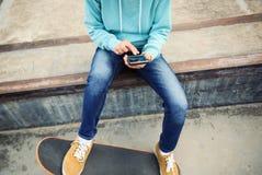 Teléfono móvil del uso del skater en el skatepark Fotos de archivo libres de regalías