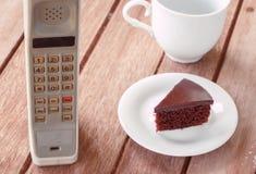 Teléfono móvil del vintage con la taza Fotografía de archivo libre de regalías