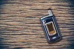 Teléfono móvil del vintage puesto en de madera imagen de archivo libre de regalías