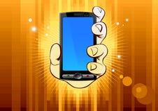 Teléfono móvil a disposición en fondo del oro Imagen de archivo libre de regalías