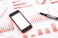 Teléfono móvil en blanco en gráficos, cartas, datos y negocio rojos con referencia a Imagen de archivo