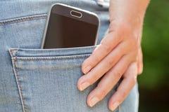 Teléfono móvil en bolsillo Fotografía de archivo libre de regalías