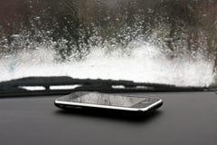Teléfono móvil en coche con lluvia imagen de archivo libre de regalías