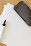 Teléfono móvil en el papel en blanco Imagenes de archivo