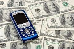 Teléfono móvil en fondo del dinero Fotos de archivo