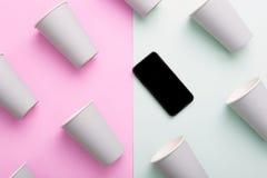 Teléfono móvil en grupo de tazas del café con leche Imagen de archivo