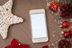 Teléfono móvil en la decoración retra de Navidad con el calendario Imagenes de archivo