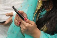 Teléfono móvil en la mano de la muchacha del adolescente Fotos de archivo