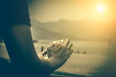 Teléfono móvil en la mano de una mujer, en puesta del sol Imagen de archivo libre de regalías