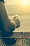 Teléfono móvil en la mano de una mujer, en puesta del sol Imagen de archivo